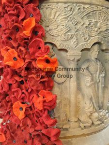 Red knitted poppies flow down the font